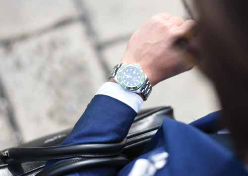 business man looking at his rolex watch wearing a blue suit