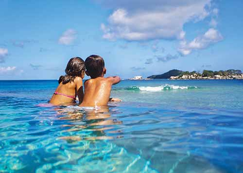 two young kids watching the waves from a infinity pool